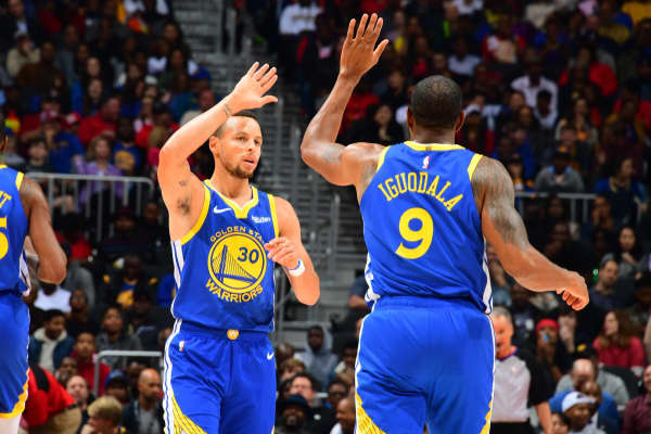 Golden State Warriors teammates Stephen Curry (L) and Andre Iguodala (R) high-five during a December 2018 game.