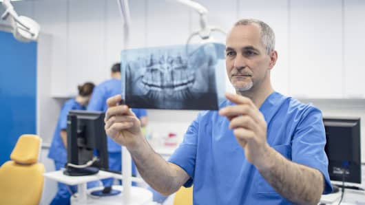 Mature male orthodontist holding X-ray image