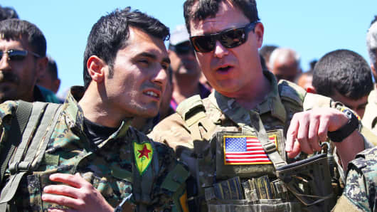 A US officer, from the US-led coalition, speaks with a fighter from the Kurdish People's Protection Units near northeastern Syrian Kurdish town of Derik, known as al-Malikiyah in Arabic, on April 25, 2017.