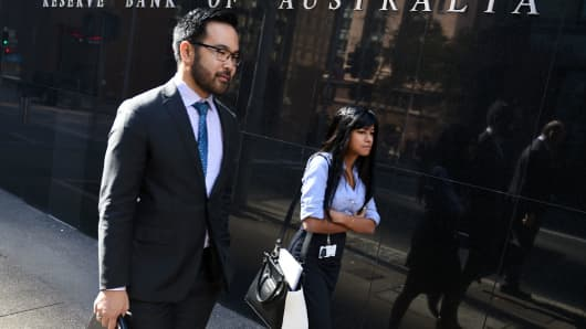 People walk past the Reserve Bank of Australia building in Sydney on May 3, 2016.