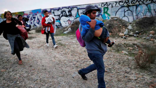 A migrant child sleeps while he is carried by family as fellow migrants, all part of the caravan of migrants who traveled from Central America with the intention of crossing into the U.S., walk to the border fence in order to cross into the U.S. from Tijuana, Mexico December 14, 2018.