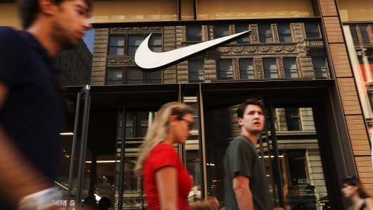 People walk by a Nike store in New York.
