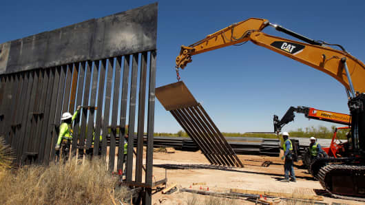 construction workers are seen next to heavy machinery while working on a new border wall in