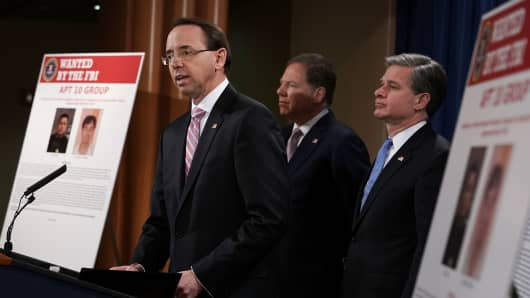 (L-R) U.S. Deputy Attorney  universal Rod Rosenstein speaks as U.S. Attorney for the Southern District of  novel York Geoffrey Berman, and FBI Director Christopher Wray listen during a  word conference to  broadcast a China related national security law enforcement action December 20, 2018 at The Justice Department in Washington, DC.