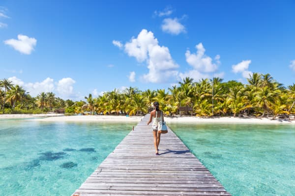 Tourist walking on jetty to tropical island