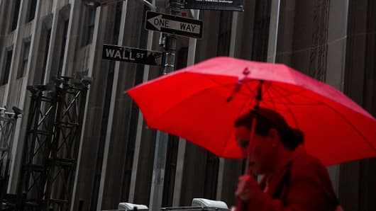 A woman carries a red umbrella while walking along Wall Street near the New York Stock Exchange (NYSE) in New York.