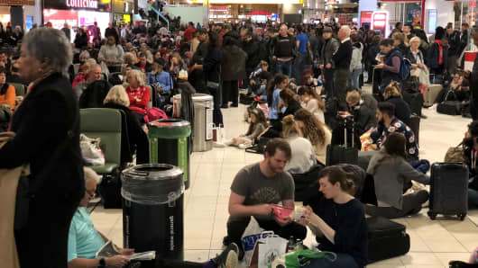 Passengers stranded at Gatwick wait for updates on their travel options on December 20, 2018.