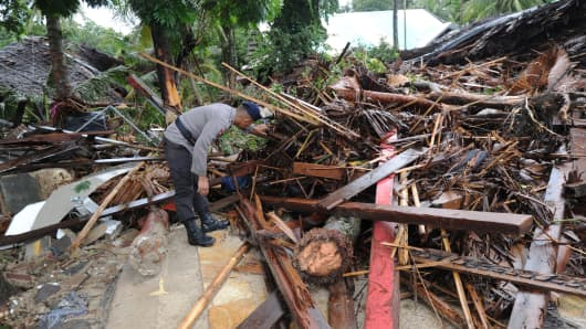 An Indonesia policeman searches for victims amongst the debris at the Mutiara Carita Cottages in Carita in Banten province on December 24, 2018, two days after a tsunami - caused by activity at a volcano known as the 'child' of Krakatoa - hit the west coast of Indonesia's Java island