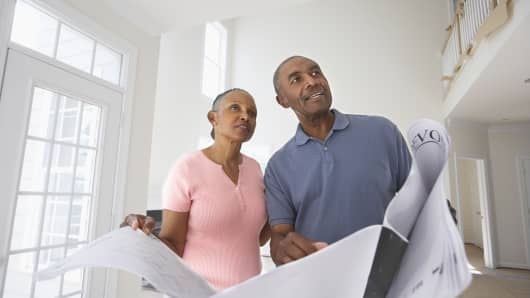 Couple standing in new home holding blueprint