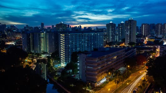 Residential and commercial buildings stand illuminated at dusk in the Kallang area of Singapore, on Saturday, Sept. 17, 2016.