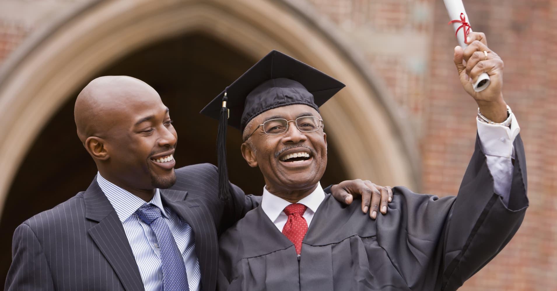African man hugging graduate father