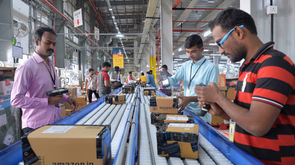 Employees of Amazon India scan packages at Amazon's newly launched fulfillment center on the outskirts of Bangalore on September 18, 2018.