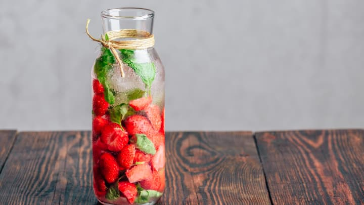 Bottle of Water Flavored with Fresh Strawberry and Basil Leaves
