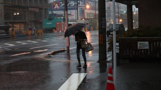 A woman walks under a heavy rain in Kagoshima, on Kyushu island, on September 30, 2018.