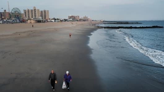 People walk along an empty beach at Coney Island on October 1, 2018 in New York City. Despite a week of warm temperatures and bright sunshine, most of the rides, stores and restaurants  have closed for the season at the iconic New York beach.