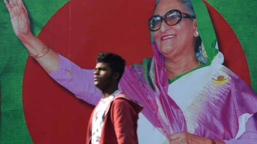 A Bangladeshi man walks past a photo of Prime Minister Sheikh Hasina, in Dhaka on December 29, 2018.