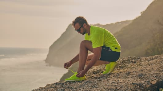 Man tying running sneakers on a tropical exotic cliff.