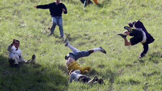 Contestants in the men's race chase a Double Gloucester Cheese down the steep gradient of Cooper's Hill during the annual tradition of cheese-rolling in Brockworth, Gloucestershire, England.