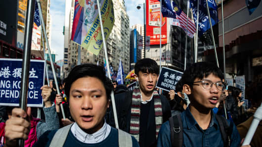 Pro-independence activists Wayne Chan (L) and former lawmaker Baggio Leung (C) chant slogans during the annual New Year's Day pro-democracy rally in Hong Kong on January 1, 2019.