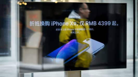 A man is reflected on a screen showing the iPhone XR at an Apple store in Beijing on January 3, 2019.