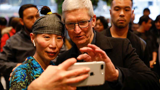 Tim Cook, Chief Executive Officer of Apple Inc., takes a selfie with a customer and her iPhone as he visits the Apple Store in Chicago, Illinois, U.S., March 27, 2018.