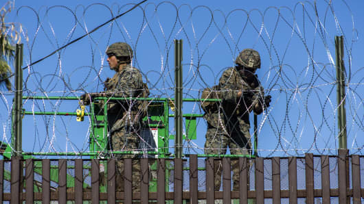 U.S. Army soldiers are seen from the Mexican side fortifying US-Mexico border fence with barbed wire  on November 26, 2018 in Mexicali, Mexico.