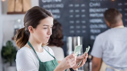 Young female barista has a disappointed expression on her face as she counts her tips at the end of the day.