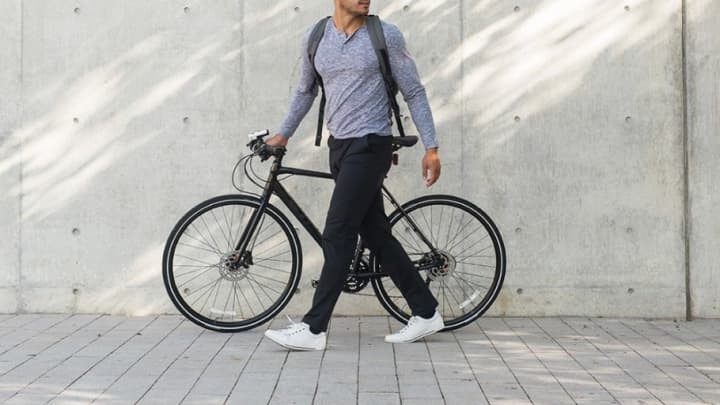 A man wears Rhone clothing while walking his bike to work. 6a05d91a4