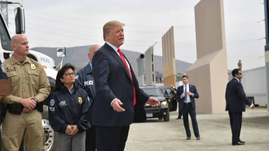 President Donald Trump (C) inspects border wall prototypes in San Diego, California on March 13, 2018.