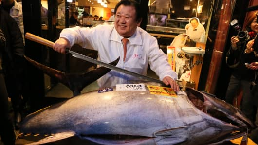 Kiyoshi kimura, president of Kiyomura K.K, poses for photos with a 180.4 kilograms (397 pounds) fresh tuna after this year's first auction at Tsukiji Market on January 5, 2015 in Tokyo, Japan. A fresh whole tuna weighing 180.4 kilograms (397 pounds), sold for 4.51 million yen (approximately $37,500) by Sushi Zanmai, a Tokyo-based sushi chain operator.
