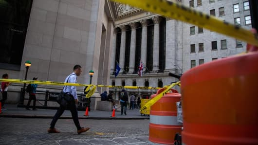 Pedestrians walk on Wall Street near the New York Stock Exchange (NYSE) in New York.