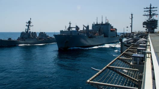 Photograph of guided-missile destroyer USS McCampbell, dry cargo/ammunition ship USNS Cesar Chavez and aircraft carrier USS Ronald Reagan during a replenishment-at-sea exercise in waters off the coast of Japan, May 15, 2018