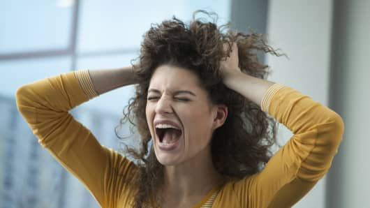 Screaming young woman with hands in hair