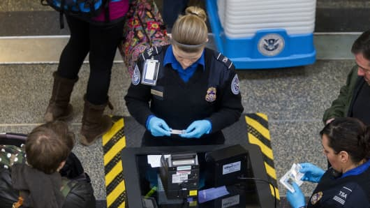 Transportation Security Administration (TSA) officers check passenger's identification at a security checkpoint at Ronald Reagan National Airport (DCA) in Washington, D.C.