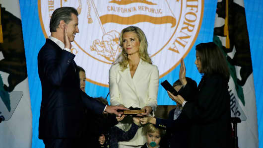 California Governor Gavin Newsom takes the oath of office from state Supreme Court Chief Justice Tani Gorre Cantil-Sakauye as his wife Jennifer Siebel Newsom looks on during his inauguration Monday, Jan. 7, 2019, in Sacramento, Calif.