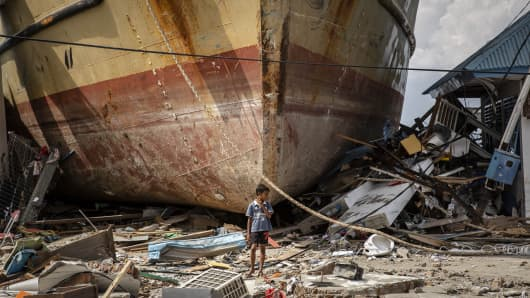 A boy stands in front of a stranded ship after a deadly tsunami struck the area on October 2, 2018 in Donggala, Central Sulawesi, Indonesia.