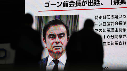 Pedestrians walk past a big screen showing images of Former Nissan Motor Co. Chairman Carlos Ghosn in a news program on Jan. 8, 2019 in Tokyo, Japan.