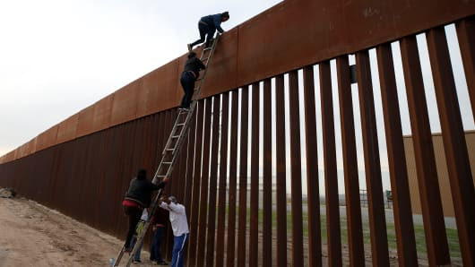 Migrants from Honduras, part of a caravan of thousands from Central America trying to reach the United States, climb a border fence to cross illegally from Mexico to the U.S., in Tijuana, Mexico, December 21, 2018.