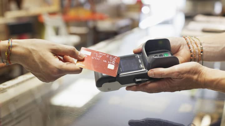 Cropped view of womens hand using credit card to make contactless payment on chip and pin machine