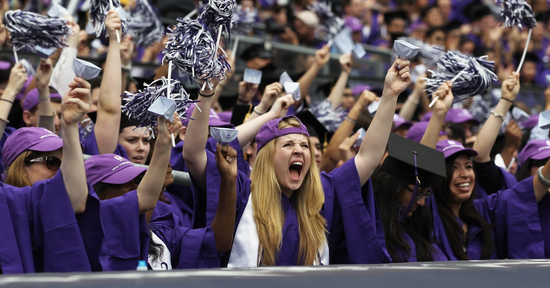 Graduating students cheer at New York University's commencement ceremony at Yankee Stadium.