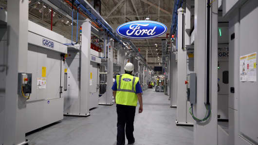 An employee walks past a Ford logo in the yet-to-be-completed engine production line at a Ford factory on January 13, 2015 in Dagenham, England.