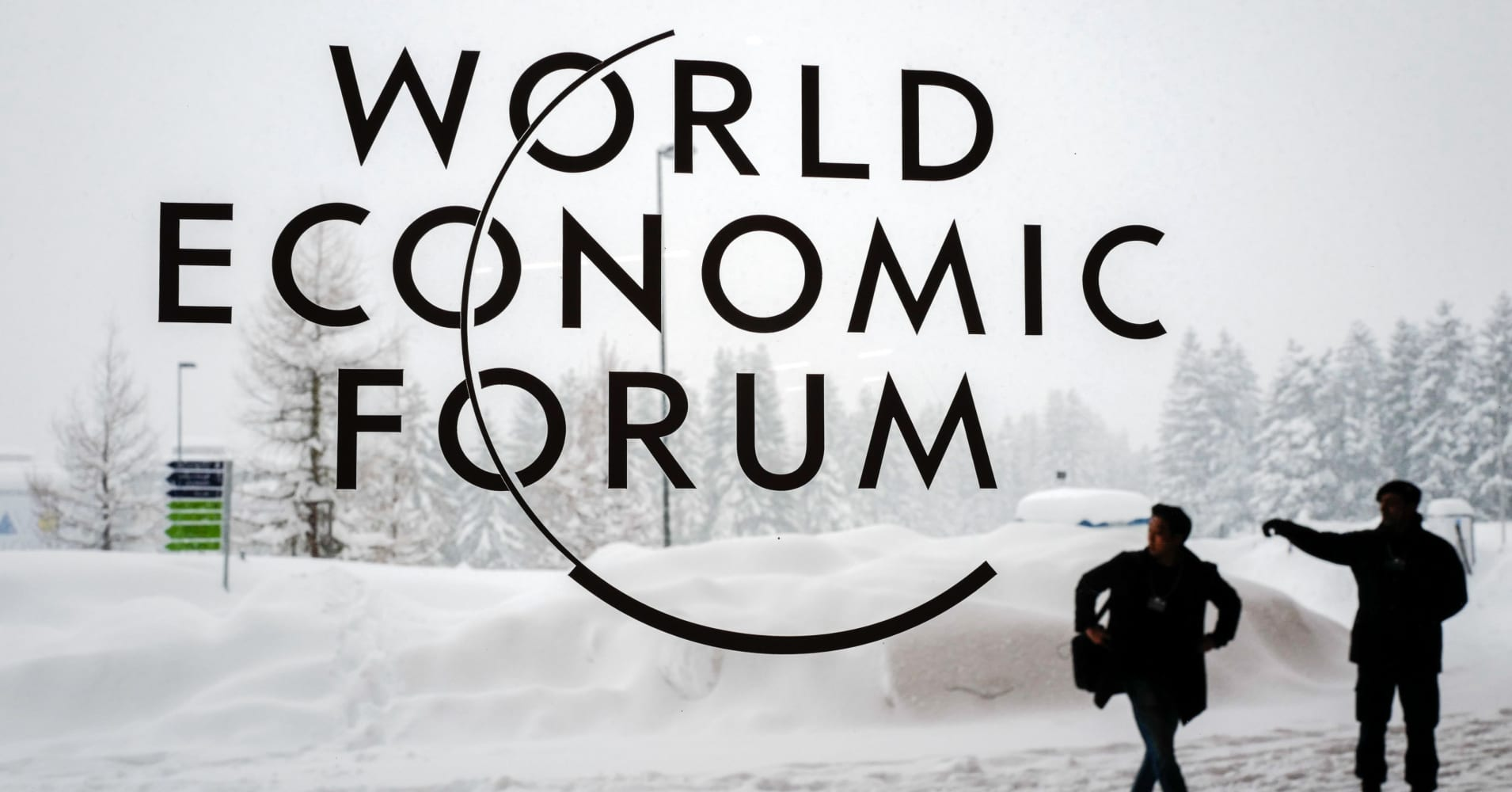 A security guard show the way to a man outside of the Davos Congress Centre under snow ahead of the opening of the World Economic Forum (WEF) 2018 annual meeting, in Davos, eastern Switzerland.
