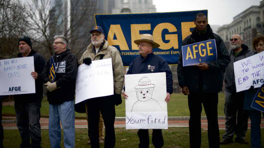 David Fitzpatrick, 64, center, a Park Ranger, holds a placard stating 'You're fired' with 'Smokey the Bear,' during a protest rally with furloughed federal workers and area elected officials in front of Independence Hall on January 8, 2019 in Philadelphia, Pennsylvania.