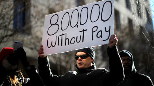 "A demonstrator holds a sign, signifying hundreds of thousands of federal employees who won't be receiving their paychecks as a result of the partial government shutdown, during a ""Rally to End the Shutdown"" in Washington, January 10, 2019."