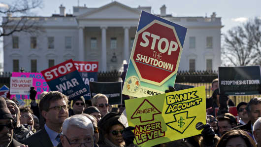 A demonstrator holds a 'Stop The Shutdown' sign during a rally with union members and federal employees to end the partial government shutdown outside the White House in Washington, D.C.