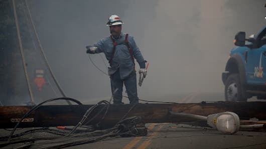 A PG&E worker attempts to clear a fallen utility pole from Pentz Road in Paradise, Calif., after it was felled by the Camp Fire, Thursday, November 8, 2018.