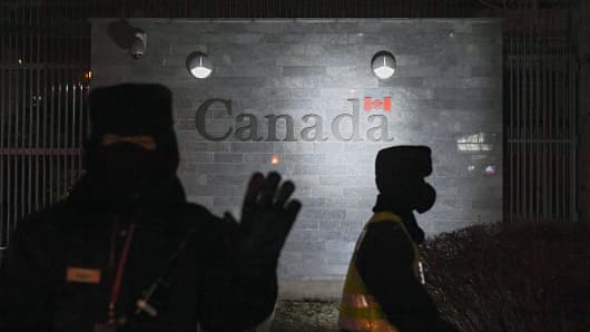 A guard tries to block photos being taken as he and a policeman patrol outside the Canadian embassy in Beijing on January 14, 2019. A Chinese court sentenced a Canadian man to death on drug trafficking charges on January 14, 2018 after his previous 15-year prison sentence was deemed too lenient, a ruling likely to deepen a diplomatic rift between Ottawa and Beijing.