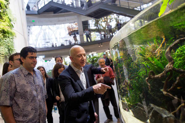 Jeff Bezos, founder and chief executive officer of Amazon points to an aquarium while touring the Spheres during opening day ceremonies at the company's campus in Seattle, Washington, in 2018. The Spheres, a new gathering and working space for Amazon employees located in the heart of the downtown Seattle Amazon campus, contains hundreds of plant species and maintains a tropical climate similar to Costa Rica.