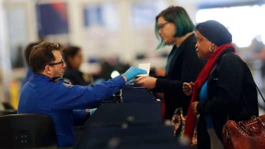 A Transportation Security Administration employee checks in air travelers at Hartsfield Jackson Atlanta International Airport Monday, Jan. 7, 2019, in Atlanta.