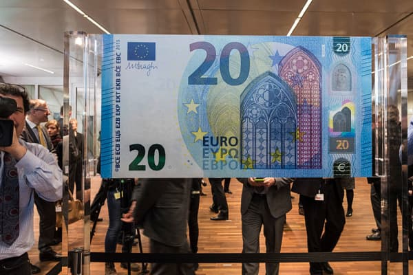 Guests and journalists observe a facsimile of the twenty euros banknote of Europa series at the end of its unveiling ceremony during which ECB president Mario Draghi signed a facsimile, in the ECB headquarters, Frankfurt, Germany, 24 February 2015.
